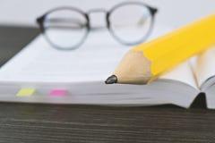 Verres de hippie pour lire sur un livre ouvert avec le grand crayon jaune Photos stock