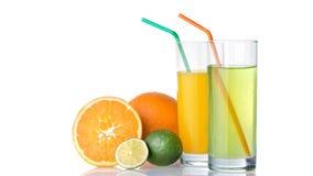 Verres de jus d'orange et de limette avec des fruits d'orange et de chaux Photos stock
