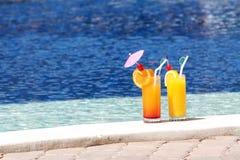 Verres de jus de fruit sur le fond de l'eau bleue Photo stock