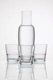 Verres de l'eau sur la table en verre Photographie stock libre de droits