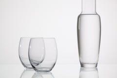Verres de l'eau sur la table en verre Images stock
