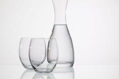 Verres de l'eau sur la table en verre Photographie stock