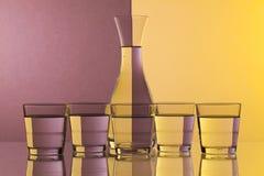 Verres de l'eau sur le bureau en verre Photo stock