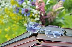 Verres de lecture avec les livres ouverts Image stock