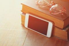 Verres de lecture, pile de vieux livres et smartphone au-dessus de table en bois, rétro image filtrée Photo stock
