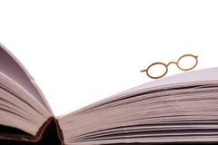 Verres de lecture sur le bord de livre Photos stock