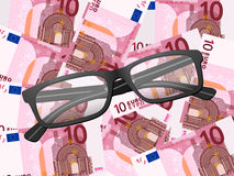 Verres de lecture sur le fond de l'euro dix Photo libre de droits