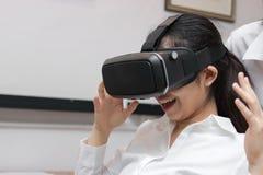 Verres de port asiatiques gais de réalité virtuelle de femme d'affaires dans le bureau photos libres de droits