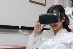 Verres de port asiatiques gais de réalité virtuelle de femme d'affaires dans le bureau image stock