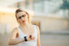Verres de port blonds de femme d'affaires parlant la montre intelligente Images stock