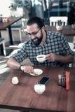 Verres de port d'homme d'affaires vérifiant le temps tout en ayant la pause-café photos libres de droits