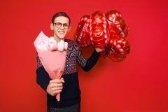 Verres de port d'un homme avec un groupe de fleurs et de ballons en forme de coeur sur un fond rouge Jour du `s de Valentine images stock