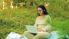 Verres de port d'une femme de brune avec des verres en clairière de forêt fonctionnant avec un ordinateur portable banque de vidéos