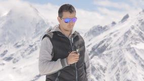 Verres de port de jeune homme, fumant la cigarette électronique sur des montagnes d'un fond banque de vidéos