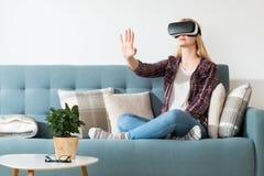 Verres de port de réalité virtuelle de femme attirante se reposant sur un divan Casque de réalité virtuelle Réalité virtuelle de  Image libre de droits