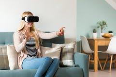 Verres de port de réalité virtuelle de femme attirante se reposant sur un divan Casque de VR Photos libres de droits