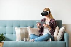 Verres de port de réalité virtuelle de femme attirante se trouvant sur un divan Casque de réalité virtuelle Concept de réalité vi Photo libre de droits