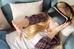 Verres de port de réalité virtuelle de femme attirante se trouvant sur un divan Casque de réalité virtuelle Réalité virtuelle de  Photos stock