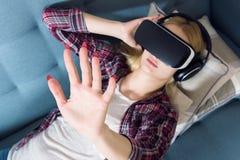 Verres de port de réalité virtuelle de femme attirante se trouvant sur un divan Casque de VR Photo libre de droits