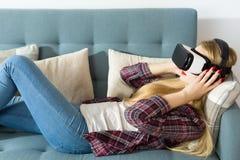 Verres de port de réalité virtuelle de femme attirante se trouvant sur un divan Concept de réalité virtuelle de mode de vie Photographie stock libre de droits