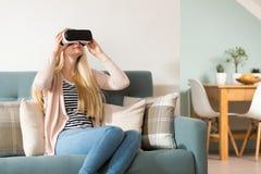 Verres de port de réalité virtuelle de femme se trouvant sur un divan Casque de réalité virtuelle Concept de réalité virtuelle de Images stock