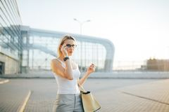 Verres de port de femme d'affaires parlant les horloges intelligentes Images libres de droits