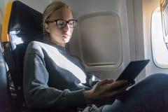 Verres de port de femme lisant sur l'e-lecteur numérique tout en voyageant en avion images stock