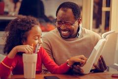 Verres de port de père sentant le livre de lecture mémorable pour la fille images libres de droits