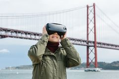 Verres de port de réalité virtuelle de jeune belle fille 25ème du pont d'avril à Lisbonne à l'arrière-plan Le concept de Images libres de droits