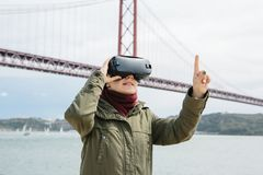Verres de port de réalité virtuelle de jeune belle fille 25ème du pont d'avril à Lisbonne à l'arrière-plan Le concept de Photo stock
