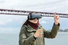 Verres de port de réalité virtuelle de jeune belle fille 25ème du pont d'avril à Lisbonne à l'arrière-plan Le concept de Photos libres de droits