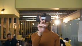 Verres de port de réalité virtuelle de jeune femme caucasienne faisant défiler dans le ciel dans le bureau banque de vidéos