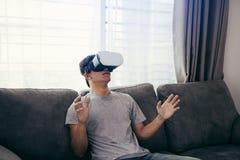 Verres de port de r?alit? virtuelle de jeune homme asiatique au salon pour admirer la r?alit? virtuelle photos libres de droits