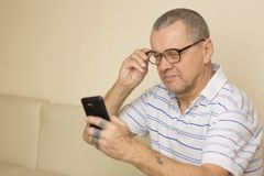 Verres de port de vieil homme pour utiliser son smartphone avec les yeux en partie c Photo stock