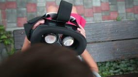 Verres de réalité virtuelle de prise de petit garçon dans ses hsnds banque de vidéos