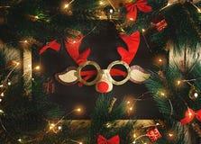 Verres de renne de Noël sur le tableau noir entouré par Noël photos stock