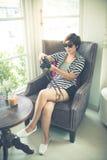 Verres de soleil de femme asiatique et photo de port de prise au café photographie stock libre de droits