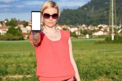 Verres de soleil de port de belle femme tout en tenant à disposition un smartphone image libre de droits