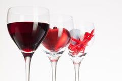 Verres de vin avec la boule de vin rouge, de coeur et de golf Photos stock