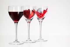 Verres de vin avec la boule de vin rouge, de coeur et de golf Images libres de droits