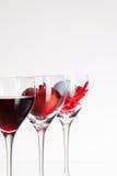 Verres de vin avec la boule de vin rouge, de coeur et de golf Images stock