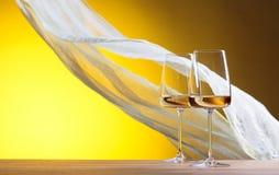 Verres de vin blanc sur un fond jaune Photos libres de droits