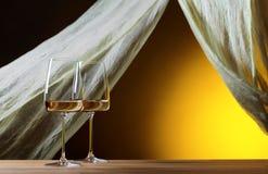 Verres de vin blanc sur un fond jaune Photographie stock