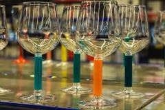 Verres de vin colorés transparents d'arc-en-ciel verts et bleus et couleurs oranges avec de belles réflexions photos libres de droits