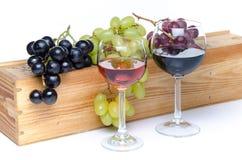Verres de vin devant une boîte en bois avec des raisins Photos stock