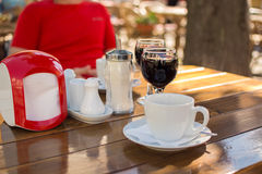 Verres de vin et d'une tasse de café à un café extérieur avec un bl photographie stock