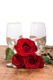 Verres de vin et trois roses rouges Photo stock