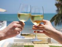 Verres de vin résonnants d'homme et de femme avec du vin blanc Photographie stock