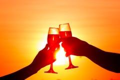 Verres de vin résonnants d'homme et de femme avec le champagne au coucher du soleil Image libre de droits