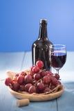 Verres de vin rouge avec des raisins rouges et une bouteille de vin sur le bleu Photos libres de droits